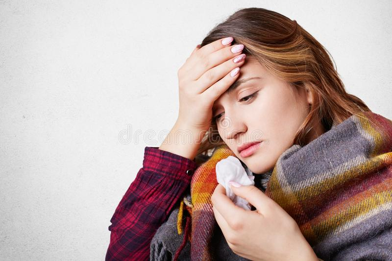 People, disease, healthcare concept. Stressful woman has flu, suffers from running nose, bad cold and headache, wrapped in wool pl. Aid, looks down, over white stock images