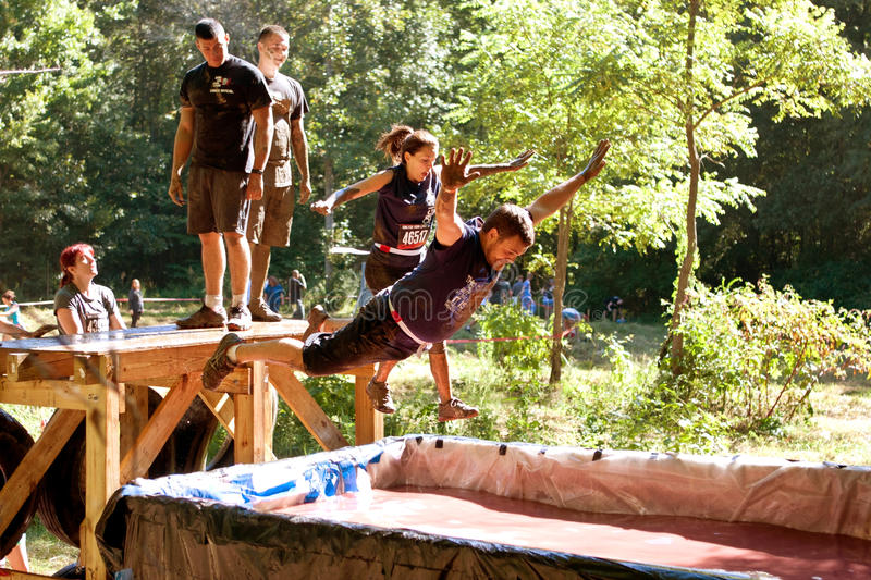 People Dive Into Blood Pit On Zombie Obstacle Course Race royalty free stock photo