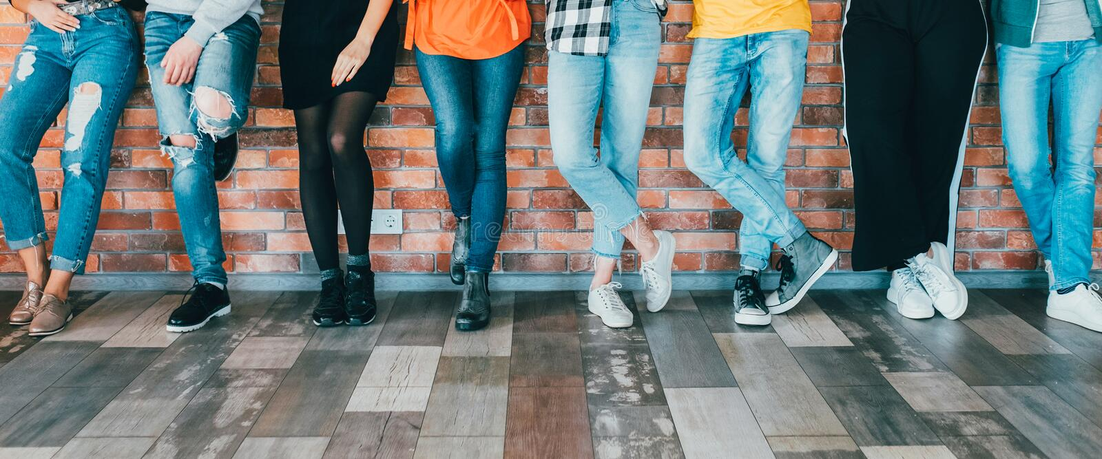 People diversity men women leg relaxed millennials. People diversity. Cropped shot of men women legs in jeans. Group standing leaning against brick wall. Relaxed royalty free stock photos