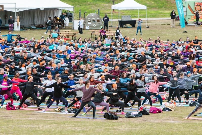 People Do Warrior II Pose In Massive Outdoor Yoga Class stock photos