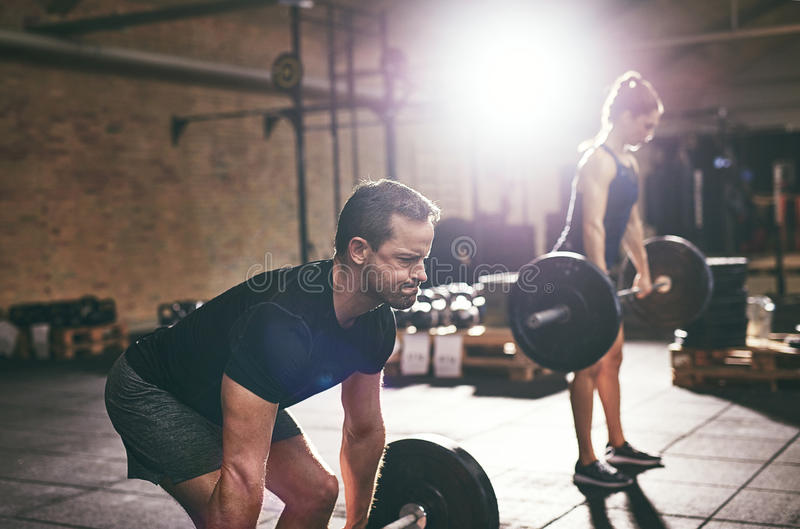 Strong people doing heavy workout with barbells royalty free stock images