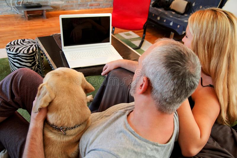 People with dog at home. Young happy couple enjoy with their Yellow labrador retriever dog at house living room, using laptop in couch. Handsome guy and girl royalty free stock images