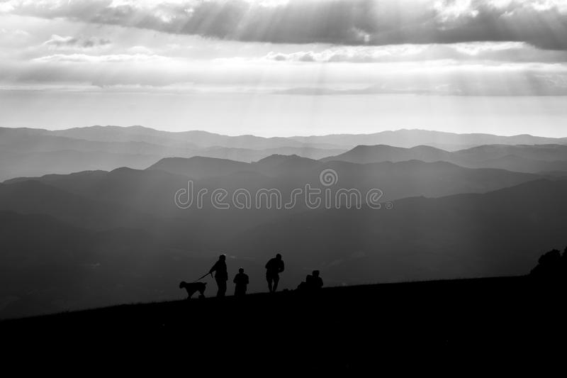 People and dog on top of a mountain royalty free stock photo