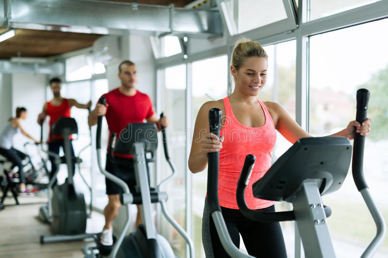 People doing on elliptical trainer in gym stock images
