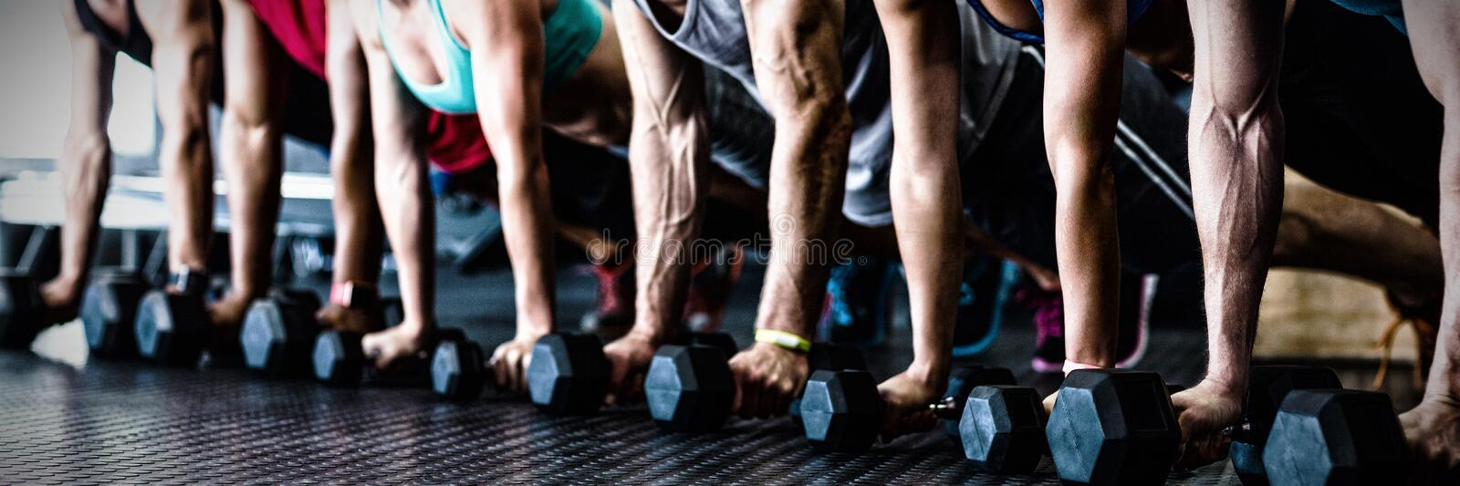 People doing push ups with dumbbell in gym stock photos