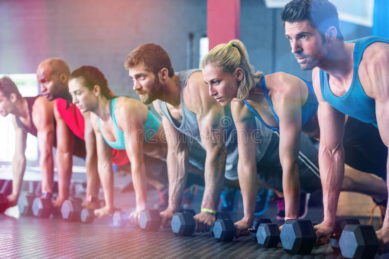 People doing push ups with dumbbell in gym royalty free stock images