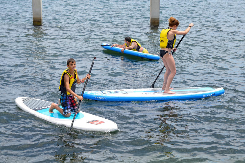 People doing Stand up paddle surfing, or boarding (SUP) stock image