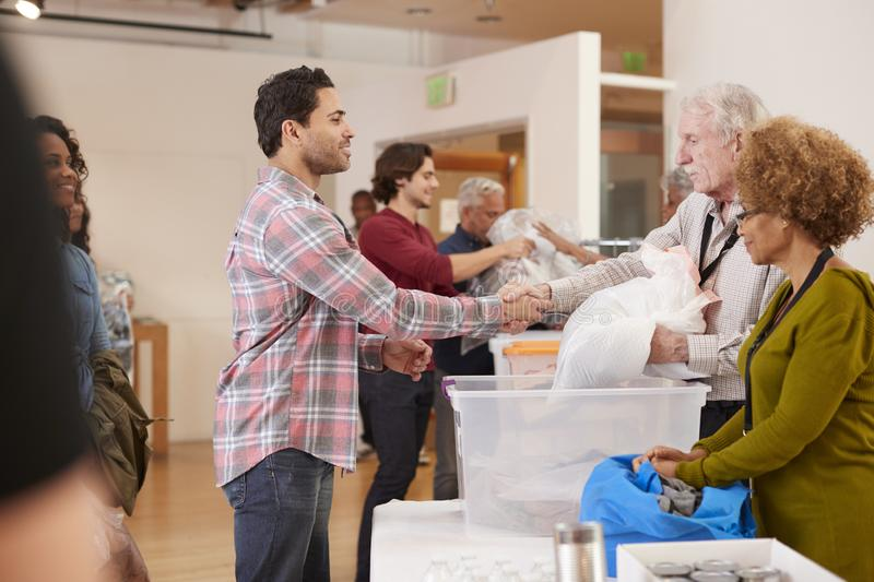 People Donating Clothing To Charity Collection In Community Center royalty free stock photography