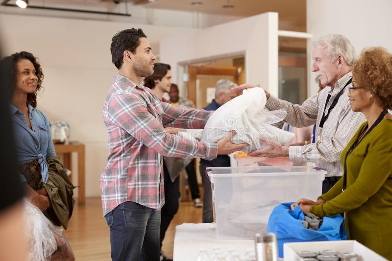 People Donating Clothing To Charity Collection In Community Center royalty free stock images