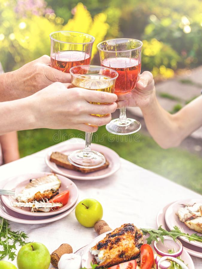 People drink rose and white wine. Dinner with grilled fish, vegetables and salads. Dinner in the backyard. Vertical shot stock images