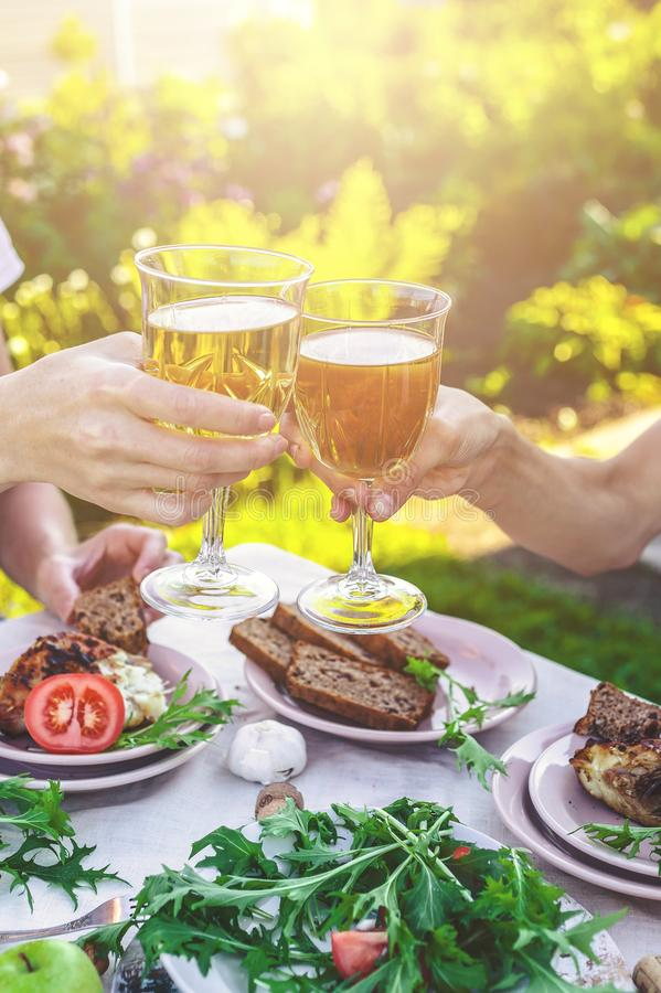 People drink white wine, eat grilled fish, fresh vegetables and herbs. Dinner in the garden concept. Vertical shot stock image