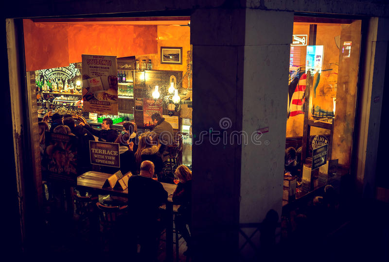 People drinking in bar in Venice, Italy. VENICE, ITALY - MARCH 12, 2016: People having fun in bar in Venice, Italy. Drinking establishment, peek view. Toned stock photography