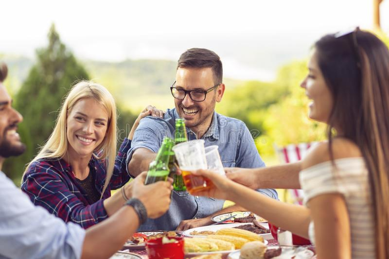 People drinking beer at barbecue party. Group of young friends having an outdoor barbecue lunch, making a toast while sitting at the table, drinking beer and royalty free stock images