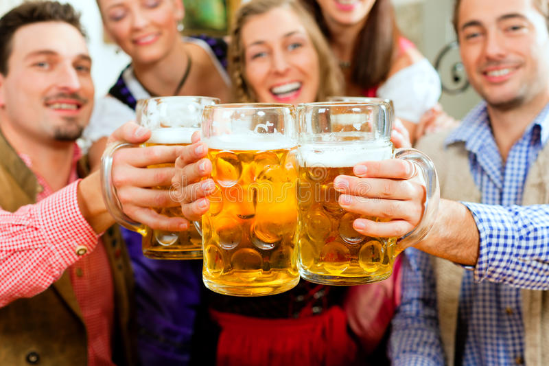 People drinking beer in Bavarian pub royalty free stock photos