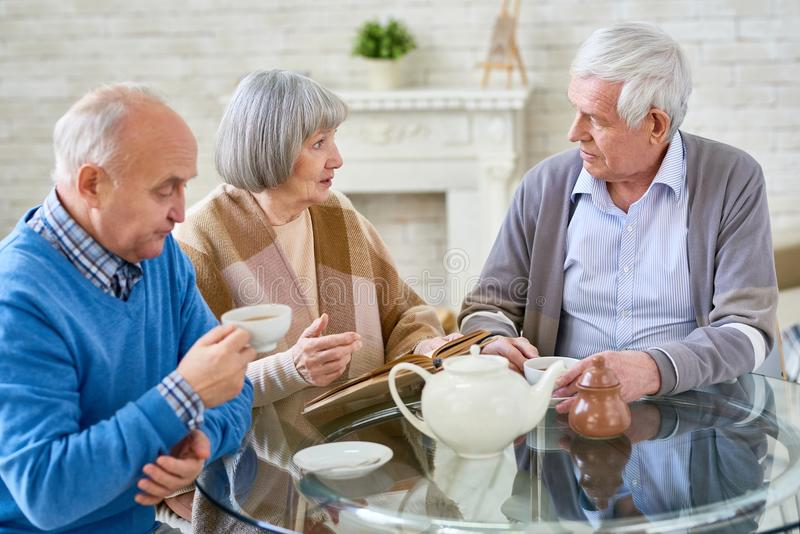 People drinking tea in senior center stock image