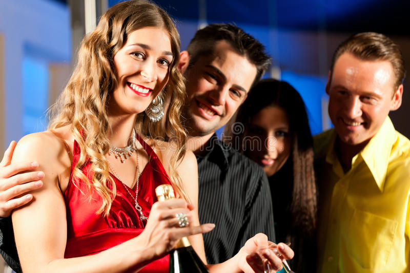People with drinks in bar or club