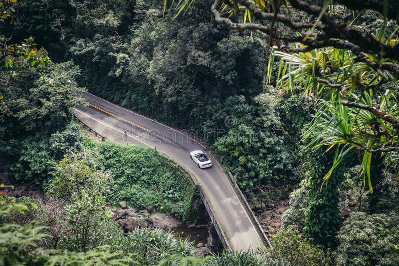 People drive luxury convertible car on scenic tropical road to Hana in Maui, Hawaii royalty free stock photo