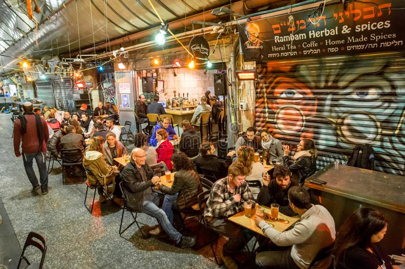 People  eat and drink on a food court in the evening  at the Machane Yehuda Market in Jerusalem, Israel royalty free stock images