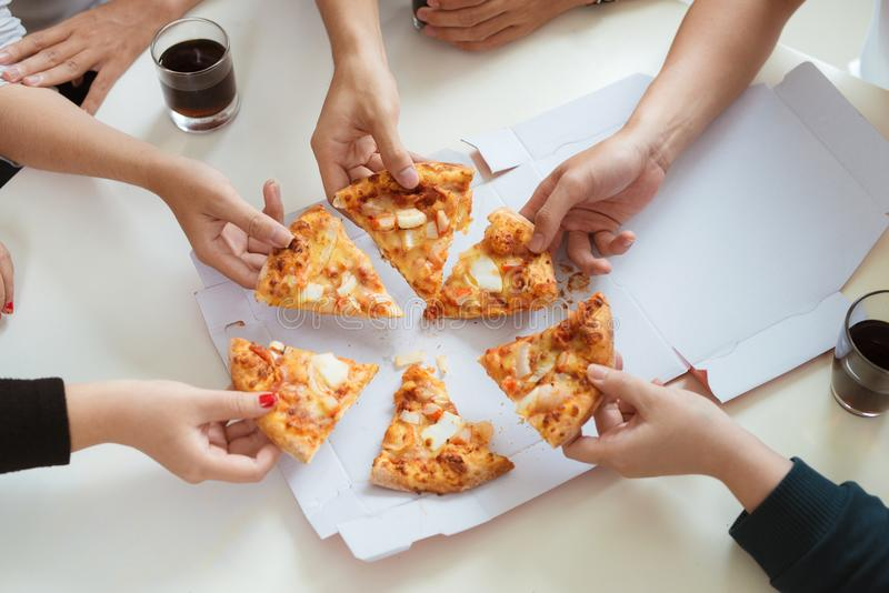 People eat fast food. Friends hands taking slices of pizza.  stock photography