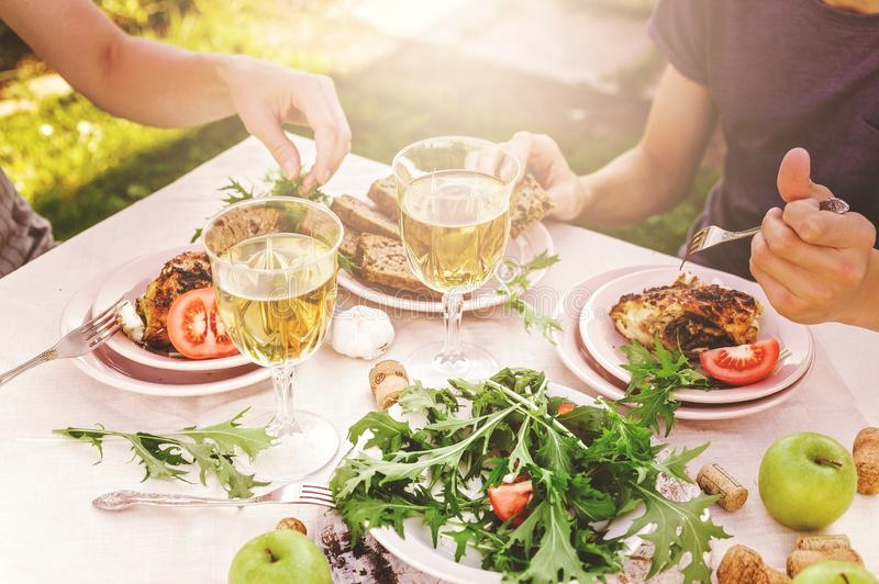 People eat in the garden at the table. Dinner concept with wine in the fresh air. Fish and salads with vegetables and herbs. stock photos
