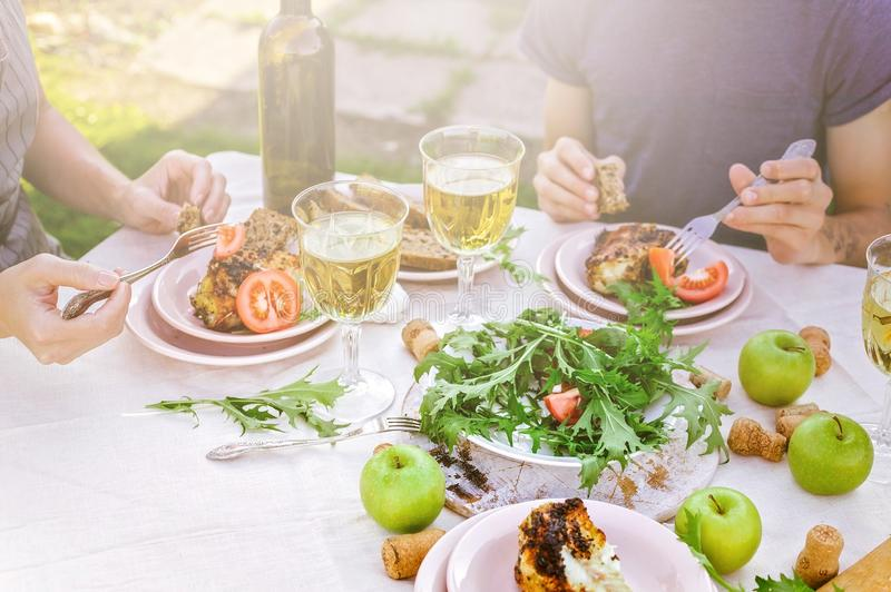 People eat in the garden at the table. Dinner concept with wine in the fresh air. Grilled sea fish and salads with vegetables and stock photos