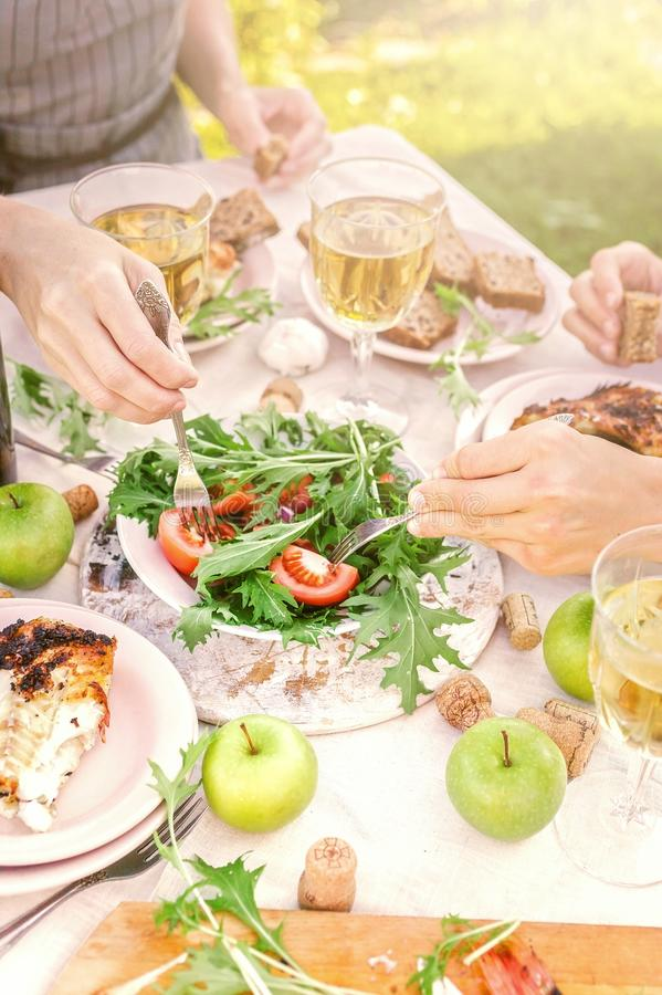 People eat in the garden at the table. Dinner concept with wine in the fresh air. Grilled sea fish and salads with vegetables and royalty free stock images