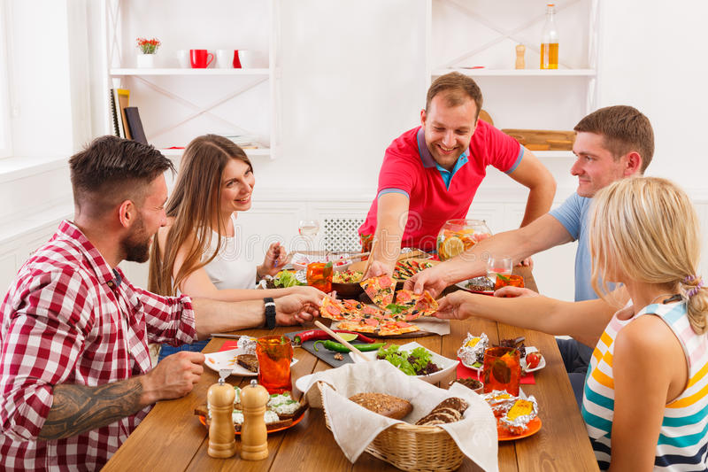 People eat pizza at festive table dinner party. Happy friends eat pizza at festive table served for party. People celebrate with catering food on wooden table royalty free stock image