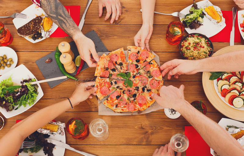 People eat pizza at festive table dinner party royalty free stock photos