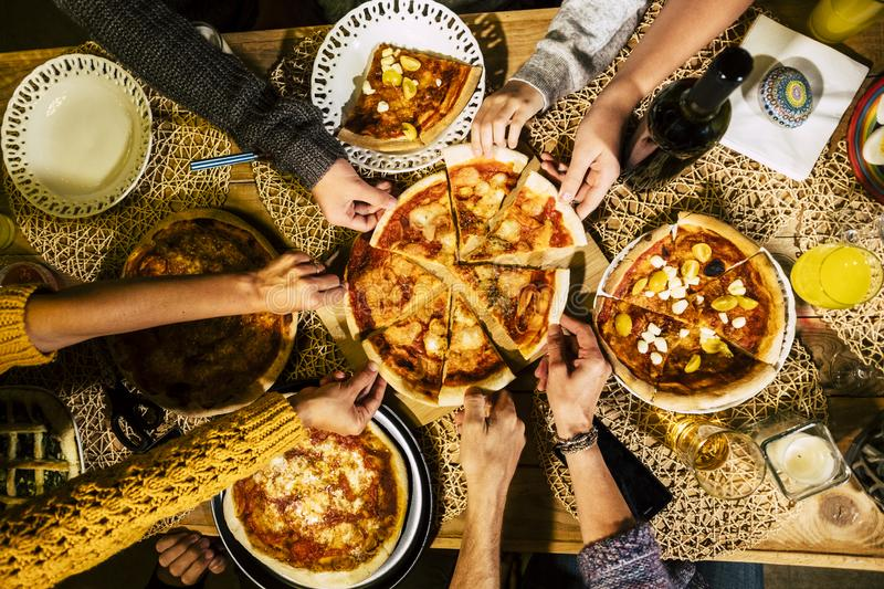 People eat pizza at festive table served for party. Friends celebrate with catering food on wooden table top view. Woman and man `. People eat pizza at festive royalty free stock images