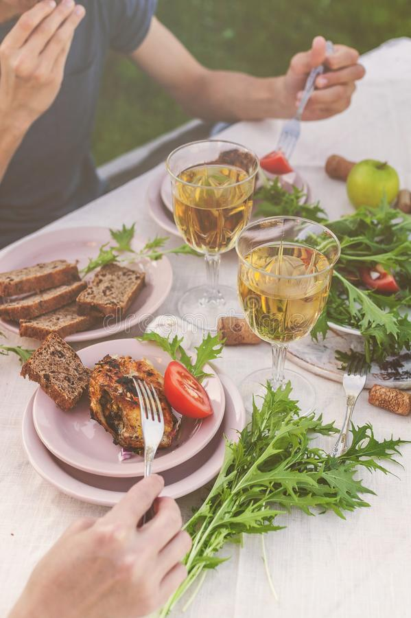 People eat at the table in the garden. Dinner at sunset with wine, grilled fish, fresh vegetables and herbs. Vertical shot royalty free stock photos
