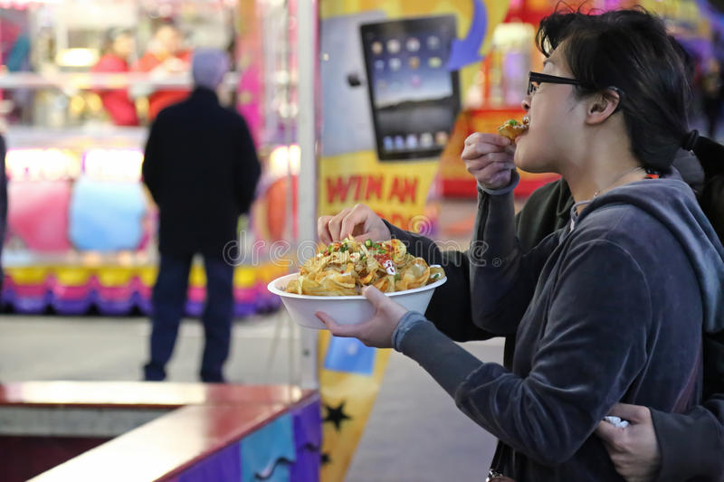 People eating curly fries at the West Coast Amusements Carnival stock image