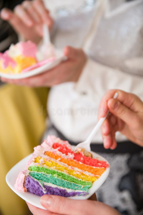 People eating delicious rainbow cake. Homemade colorful cake for birthday party. Hands with piece of cake. stock photography