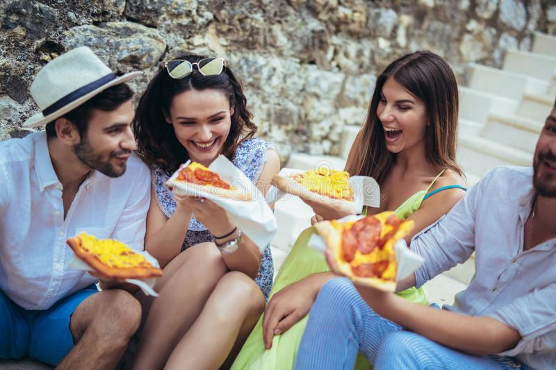 People eating fast food in city while travelling. Happy people eating fast food in city while travelling stock image