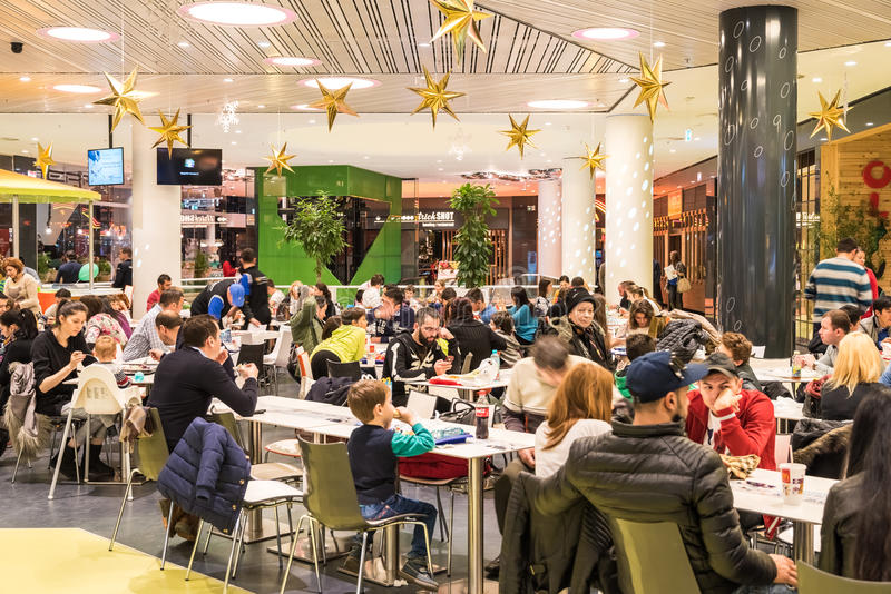 People Eating Fast Food In Shopping Mall Restaurant. BUCHAREST, ROMANIA - DECEMBER 18, 2014: People Crowd Eating Fast Food On Restaurant Floor In Luxurious royalty free stock photography