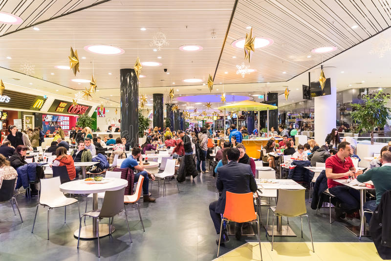 People Eating Fast Food In Shopping Mall Restaurant. BUCHAREST, ROMANIA - DECEMBER 18, 2014: People Crowd Eating Fast Food On Restaurant Floor In Luxurious royalty free stock photo