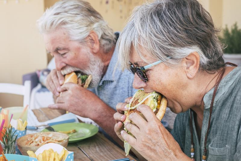 People eating hamburger junk food - Couple of senior man and woman with fast food lunch time - close up of elderly no healthy royalty free stock images