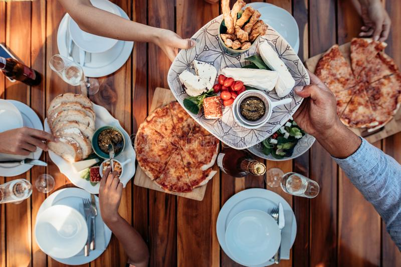 People eating meal at table served for party royalty free stock images