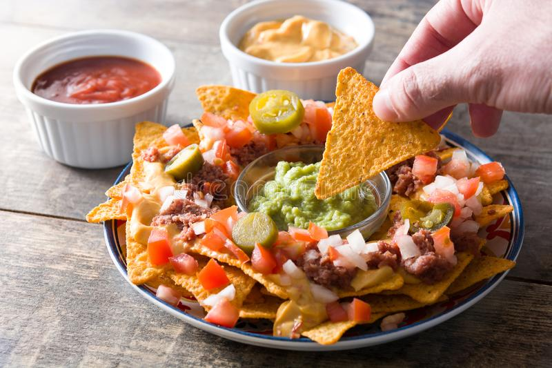 People eating mexican nachos with beef, guacamole, cheese sauce, peppers, tomato and onion in plate on wood royalty free stock photography