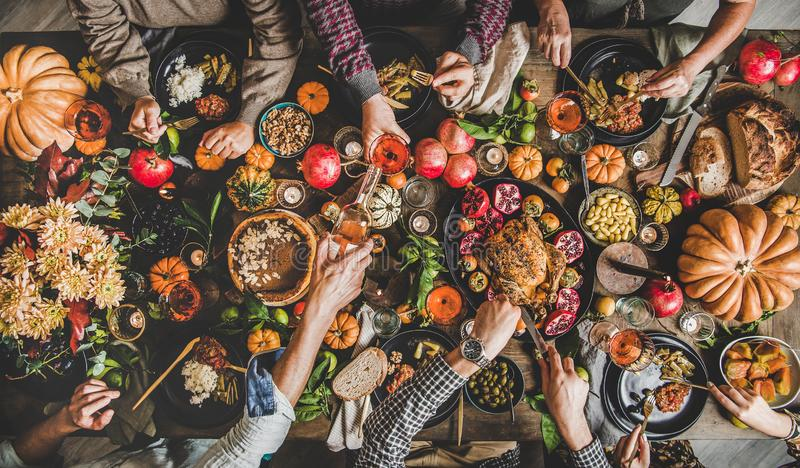 People eating and pouring wine at Thanksgiving celebration dinner table. Family celebrating Thanksgiving day. Flat-lay of eating and pouring wine peoples hands stock image