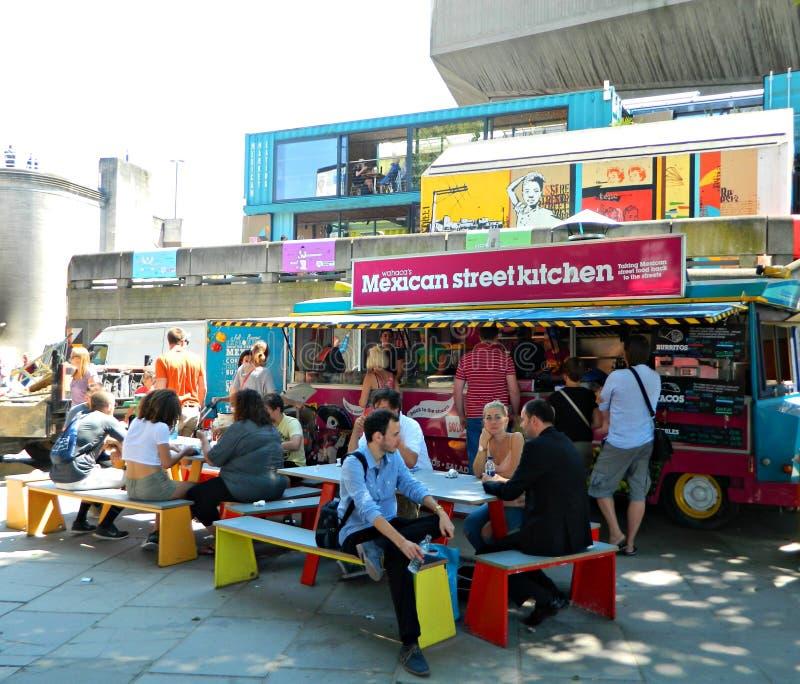People eating street food from a van in London Uk. People sitting down and standing eating mexican street food in London Uk