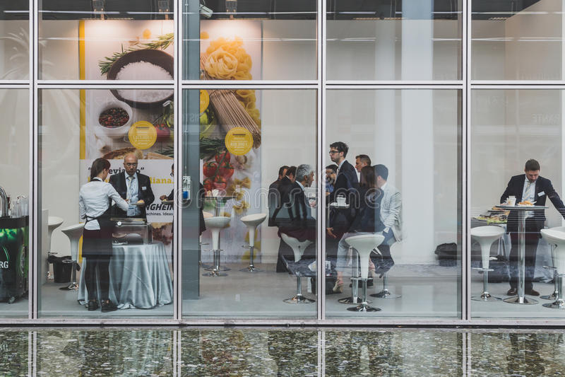 People eating at Tuttofood 2015 in Milan, Italy. MILAN, ITALY - MAY 4: People eating at Tuttofood, world food exhibition on MAY 4, 2015 in Milan stock image