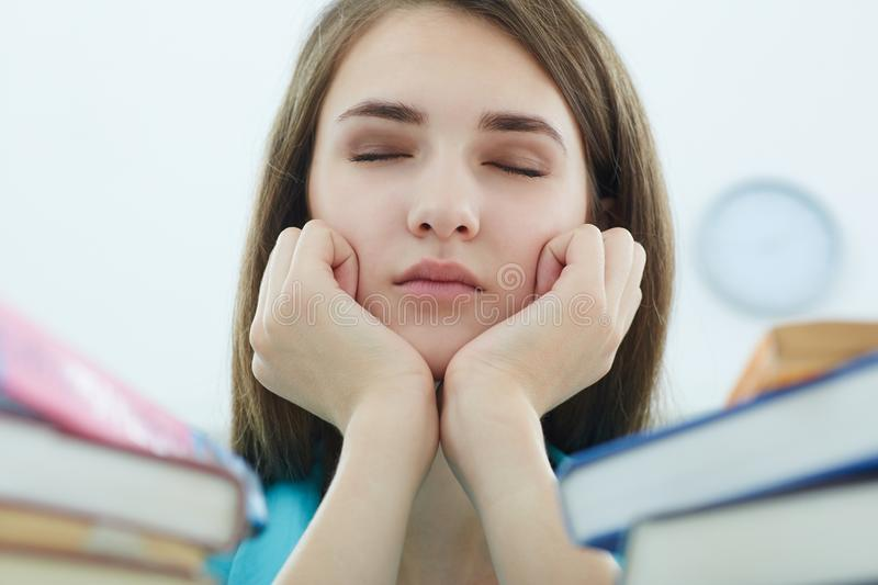 Tired student girl or young woman with books and coffee sleeping in library. People, education, session, exams and school concept - tired student girl or young stock image
