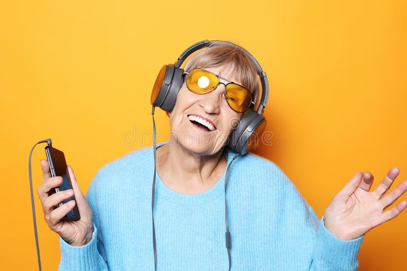 Senior woman listening to music with smartphone royalty free stock image