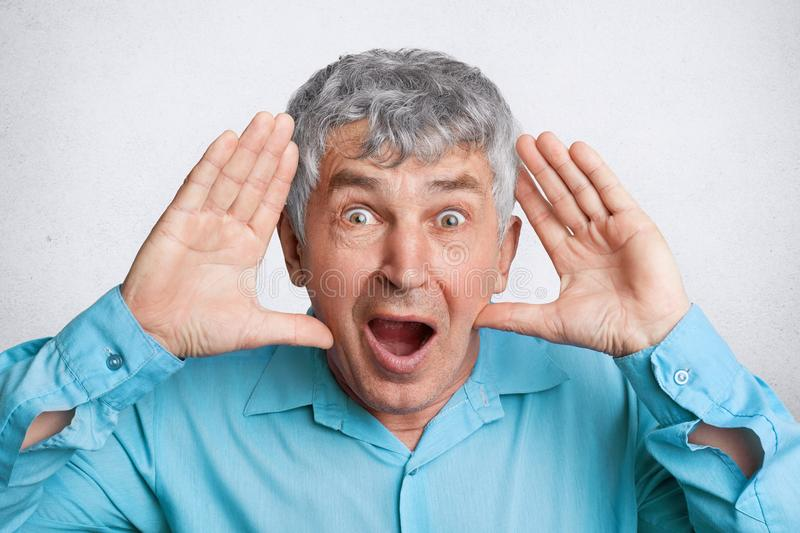 People, emotions and facial expressions concept. Amazed mature old male has bugged eyes and keeps mouth widely opened, stares at c royalty free stock image