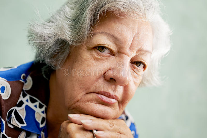 Portrait of serious old woman looking at camera with hands on ch stock images