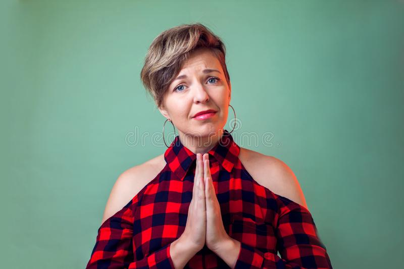 People and emotions - a portrait of  young woman with short hair keeps palms together and pleads about something. People and emotions - a portrait of sad young royalty free stock photos