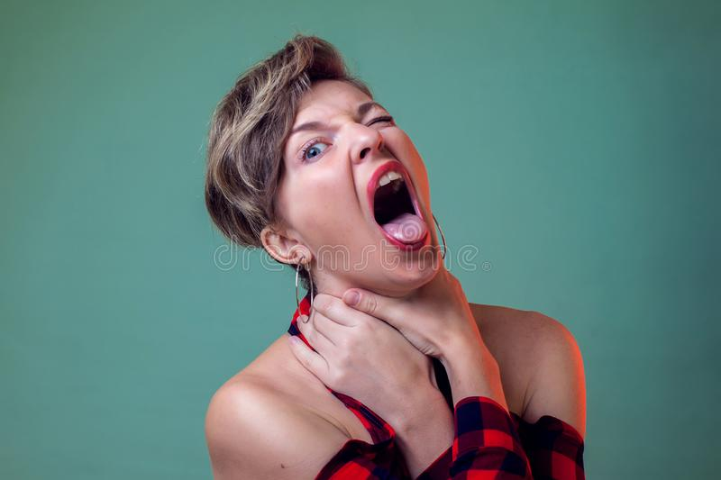People and emotions - a portrait of woman with short hair choking herself for fun. Holds hands by the neck and sticks out her stock photo