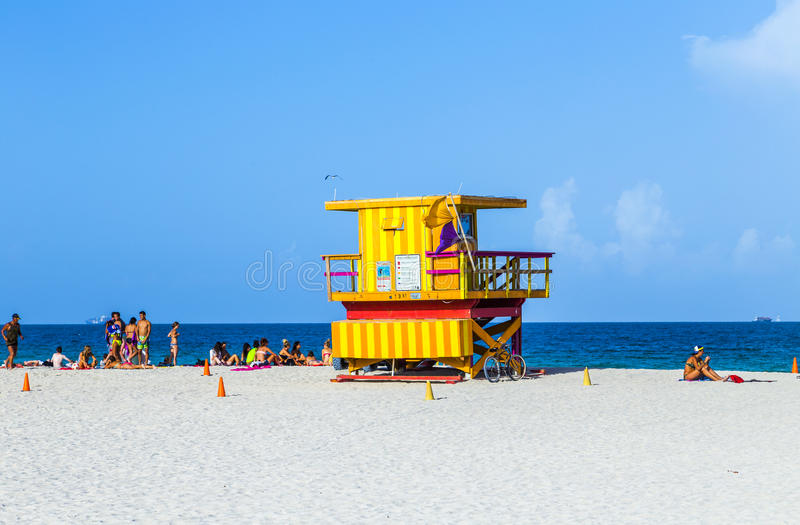 People enjoy the beach next to a lifeguard tower royalty free stock photography