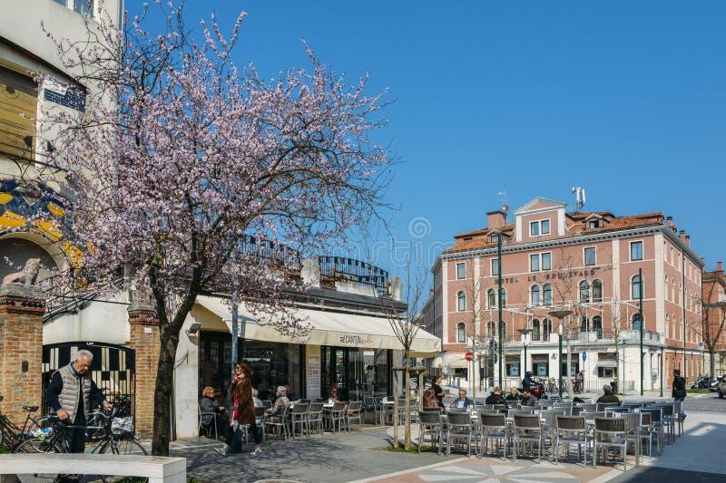 People enjoy a cafe along Santa Maria Elisabetta street, heart of the island of Lido, near to Venice. LIDO, ITALY - MARCH 28th, 2018: People enjoy a cafe along royalty free stock photography