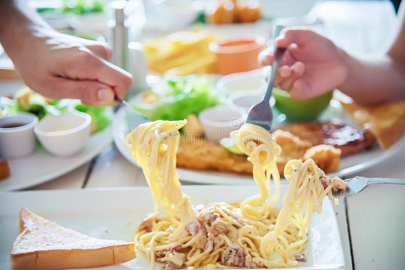 People enjoy eat spaghetti together in a big meal set. Family happy time with food concept stock photo